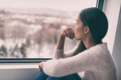 Sad women sitting near window alone
