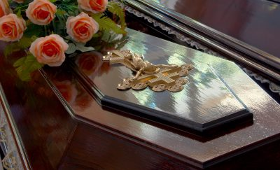 Dark wooden coffin with Jesus crucifix and roses