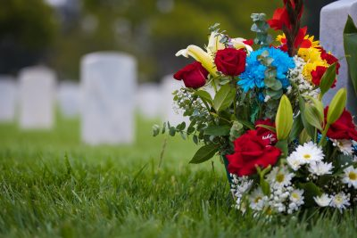 Save Download Preview white grave markers and flowers at a national cemetery