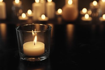 Burning candle on table in darkness