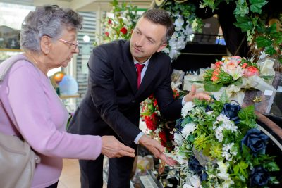 woman choosing flowers with help of funeral director